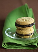 Two Chocolate Ganache Sandwich Cookies Stacked on a Glass Plate