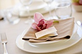 A place setting with place card and an orchid flower