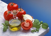 A still life of tomatoes, basil and olive oil