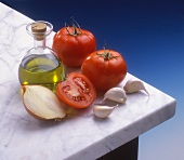 A still life of tomatoes, olive oil and garlic