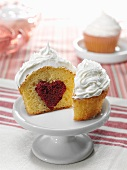 Cupcake with red velvet heart center on pedestal