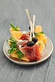 Melon slices with prosciutto and olives