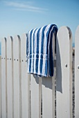 Blau-weiss gestreiftes Handtuch auf einem weissen Holzzaun am Strand