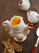 Soft Boiled Egg in a Chicken Cup with Toast on a Wood Table