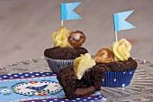 Cupcakes aus Schokoladenteig mit Vanillecreme und Fähnchen
