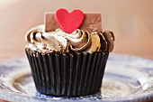 A cupcake topped with gold icing and a heart