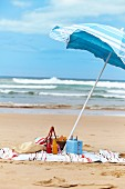 A picnic on a sandy beach with a sunshade
