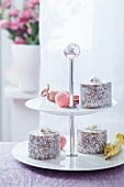 A tiered cake stand with filled chocolates and mini coconut tortes with candied daisies