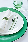 A plate decorated with a chive motif and a napkin with chives for a napkin ring