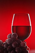 A glass of red wine and some red grapes against a red background