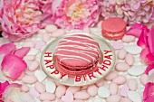 Pink Macaron mit Zuckerstreifen auf Silberteller, umgeben von Zuckermandeln, Pfingstrosen und Rosenblättern