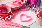 Pinkfarbene Ausstechformen, Backförmchen, Schneebesen und Messer
