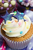 A vanilla cupcake with blue stars, glitter and sugar confetti