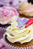 Vanilla cupcakes with hearts and colourful sugar sprinkles