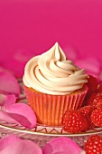 A cupcake with vanilla icing, raspberries and rose petals