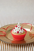 A vanilla cupcake with red chocolate beans in a red plastic case for a party