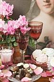 Baisergebäck, Pralinen, Weingläser, Kerzen und Cyclamen in Blumentöpfen