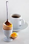 Gekochtes Ei aufgeschlagen mit Löffel und einer Tasse Kaffee