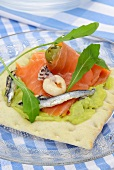 Crisp bread topped with guacamole, salmon, anchovies and seafood