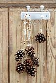 Pinienzapfen mit weihnachtlichen Bändern hängen auf Haken an einer Holzwand