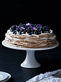 Layer cake with blueberries, blackberries and pansies