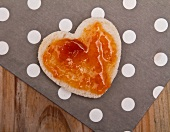 A heart cut out of bread, topped with jam, for Valentine's Day