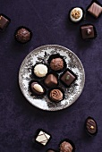 An assortment of filled chocolates, some on a plate