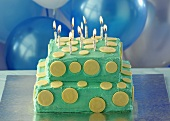 Turquoise-coloured two-tier birthday cake with candles