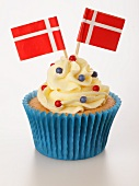 A cupcake decorated with buttercream and Danish flags