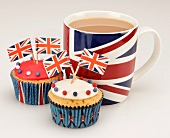 Cupcakes decorated with Union Jack flags, and a cup of tea