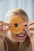 A blonde woman looking through a ring doughnut