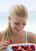 A blonde woman eating fresh berries