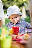 A little boy eating in the garden