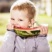 A little girl eating a slice of watermelon