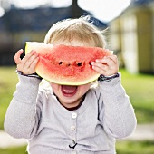 A little girl hiding behind a slice of watermelon