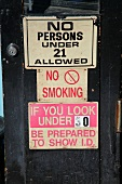Signs on the entrance door for a bar (USA)