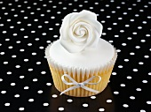 A cupcake decorated with a white rose and a ribbon