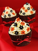 Cupcakes mit Buttercreme, Zuckerblumen und rotem Band