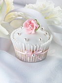 A wedding cupcake with a pink sugar rose and silver balls