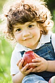 A little boy eating an apple
