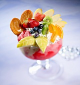 A giant ice cream sundae with strawberry ice cream, cream and lavish fruit decoration
