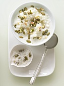 Bowl of Rice Pudding Topped with Coconut and Pumpkin Seeds