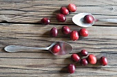 Cranberries and two spoons on a wooden surface