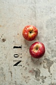 Two red apples next to a printed 'No. 1'