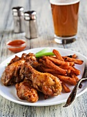 Buffalo Chicken Wings with Sweet Potatoes Fries, Celery Sticks and a Glass of Beer