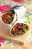 Burritos with minced meat, tomatoes, red onions and guacamole
