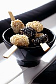 Fish skewers with black and white sesame seeds