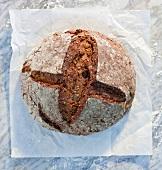 Rustikales Brot auf Papier und Marmorplatte mit Mehl
