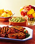 Grilled Boneless Pork Chops with Caramelized Onions; Guacamole and Tortilla Chips