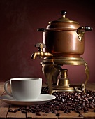 Fresh Brewed Coffee in a Cup with Coffee Beans and an Antique Brass Percolator